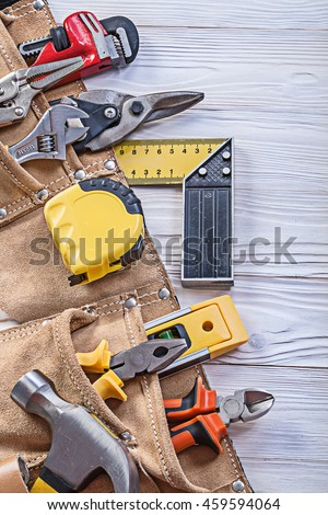 Construction tooling in tool belt on wooden board maintenance concept.