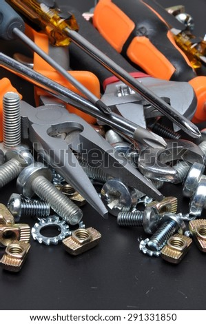 Construction tools and bolts on black metal surface
