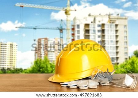 Construction tools and helmet on wooden table and building construction background