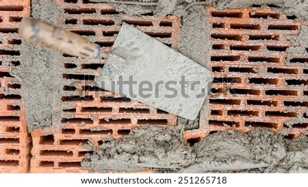 Construction tools close-up, trowel and putty knife with bricks and mortar and cement background - stock photo
