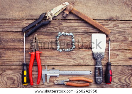 Construction tools in the form of house on wooden background. construction tools: pliers, hammer, pruner, screws, putty knife and ruler. - stock photo