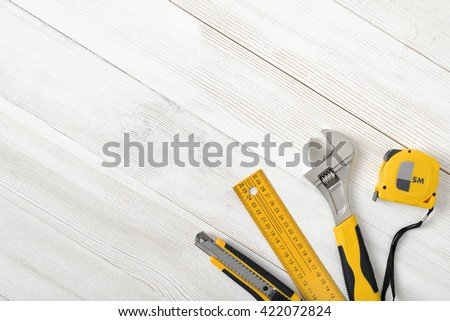 Construction tools including centimeter ruler, wrench and cutter placed in the right down corner on wooden surface with open space. Top view composition. Measurement. Fixing and cropping. Hand tool - stock photo