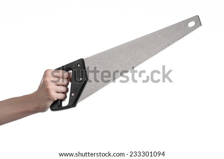 Construction topic: hand holding a saw with a black pen on a white background isolated - stock photo