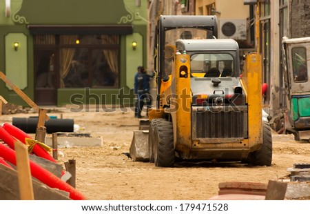 Construction vehicle in a street reconstruction with two men working in background.