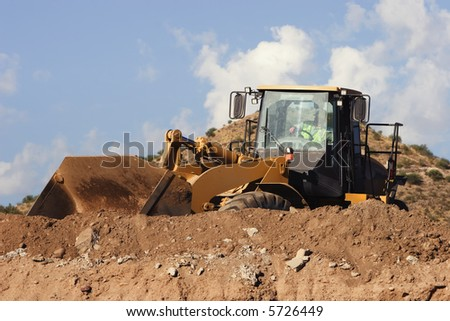 Construction vehicle moving dirt on top of a hill.