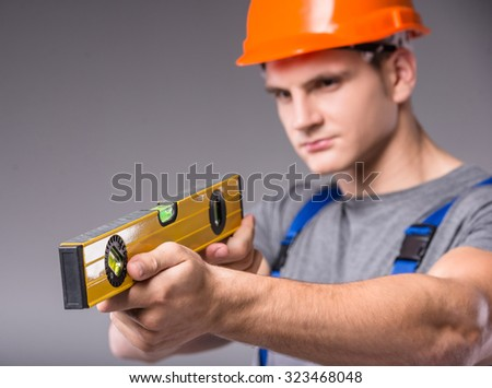 Construction work. Portrait of a young builder with tools in hand to build on gray background - stock photo
