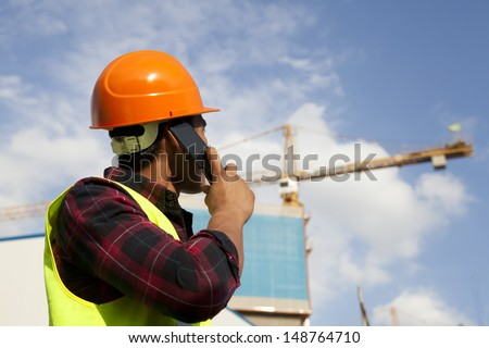 Construction worker activity with mobile phone under new building - stock photo