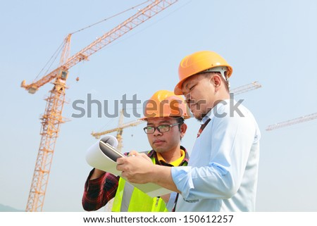Construction worker and manager checking plan at new building site