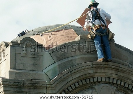construction worker applying copper to dome - stock photo