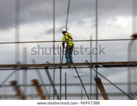 Construction worker assembling scaffolding on building site with zoom effect. - stock photo