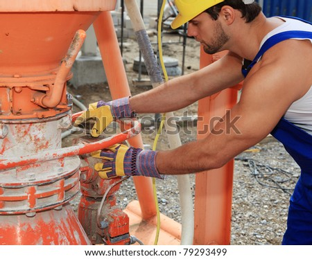 Construction worker at cement mixer. - stock photo