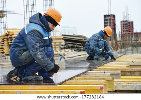 construction worker at construction site assembling falsework for concrete pouring - stock photo