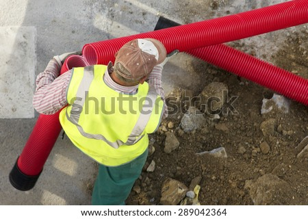 construction worker  carrying a broken pipe  in the  city  street - stock photo