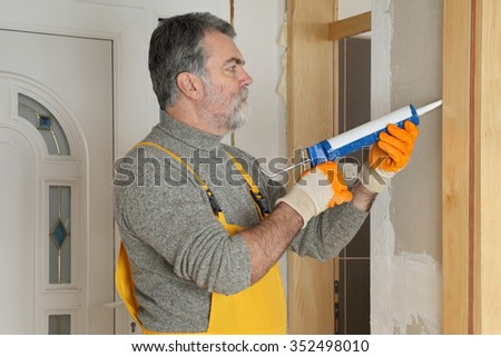 Construction worker caulking door  with silicone glue using cartridge - stock photo