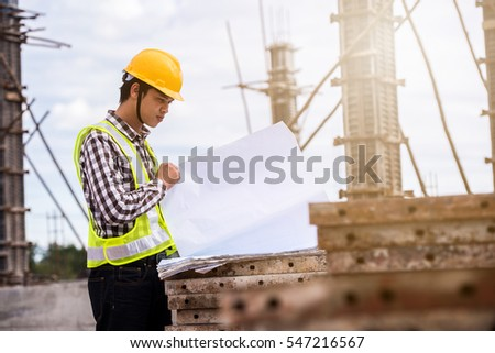 Construction worker checking blueprints on site