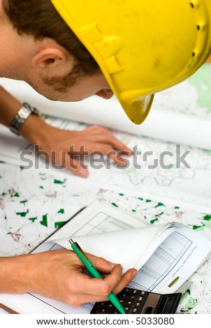 construction worker checking documents and maps