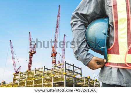 construction worker checking location site with crane on the background - stock photo