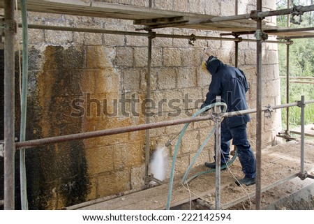 Construction worker cleaning dirtiness with high pressure washer from ancient stone wall - stock photo