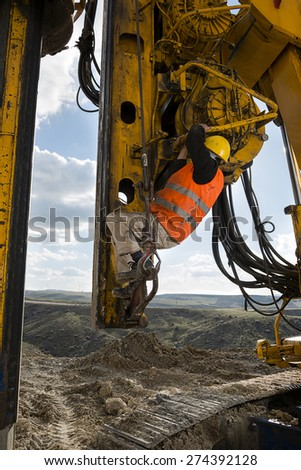 Construction worker climbing on drilling pile foundation. - stock photo