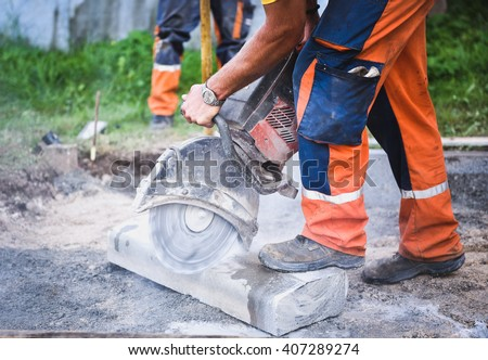 Construction worker cutting concrete paving stabs or metal for sidewalk using a cut-off saw. Profile on the blade of an asphalt or concrete cutter with workers shoes and protective gear. - stock photo