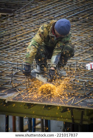 Construction worker cutting steel rods with electrical saw
