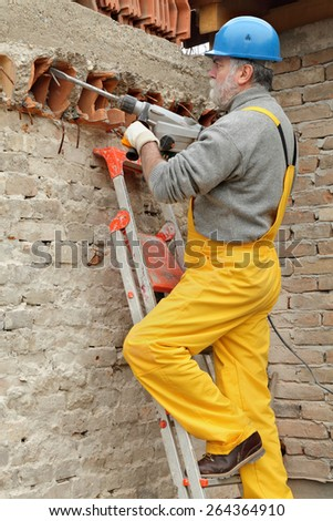 Construction worker demolishing brick wall with electric plugger, chisel hammer tool