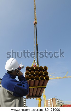 construction worker directing crane load of pipelines, building and construction industry - stock photo