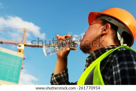 Construction worker drinking water on a location site - stock photo