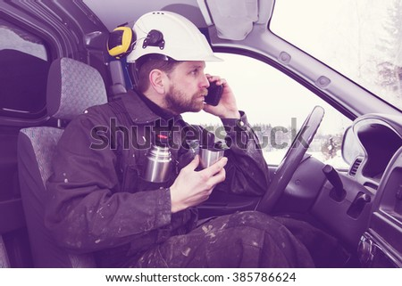 Construction worker driving a car, talking on the phone while drinking coffee in Finland. He is wearing a white helmet and he has a dirty overalls. Image includes a vintage effect. - stock photo