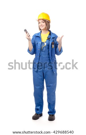construction worker, engineer or architect female in yellow hardhat and blue workwear with mobile phone showing thumb up isolated on white background. proposing service. advertisement gesture - stock photo
