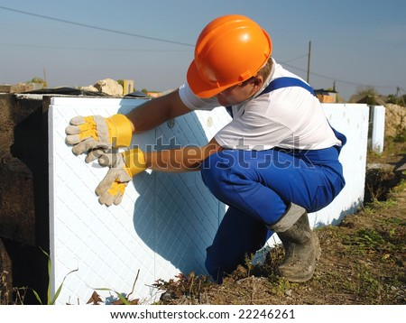 Construction worker fitting styrofoam thermal insulation panels to house foundation walls - stock photo