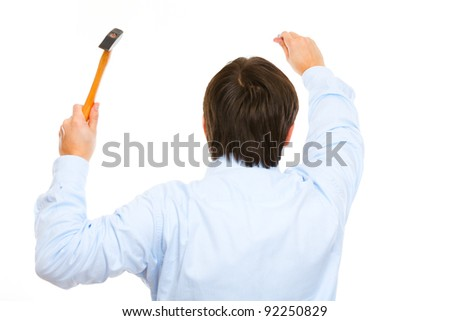 Construction worker hammering nail. Back view - stock photo