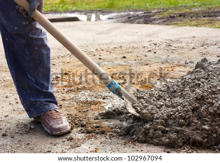 Construction worker hand  mixing concrete with a shovel