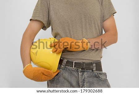 Construction worker hands holding yellow plastic helmet isolated on gray background  without gloves keep hard hat close-up  - stock photo