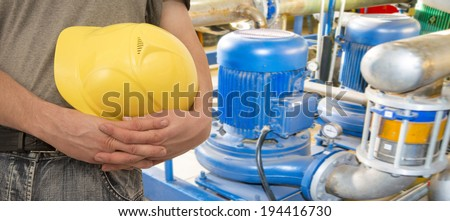 Construction worker hands holding yellow plastic helmet  on electric motor pump and pipe background   keep hard hat close-up  Copy space for inscription - stock photo
