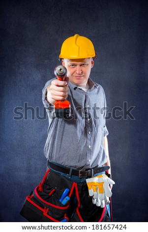 Construction worker holding a drill - stock photo