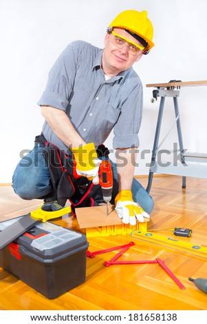 Construction worker holding a drill and drilling wooden board - stock photo