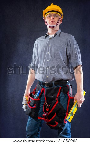 Construction worker holding a spirit level  - stock photo