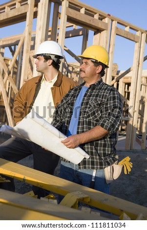 Construction worker holding blueprints - stock photo