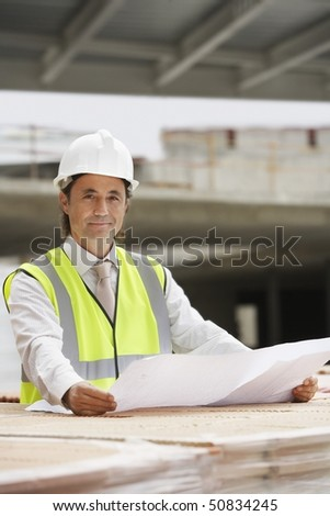 Construction worker holding building plans - stock photo