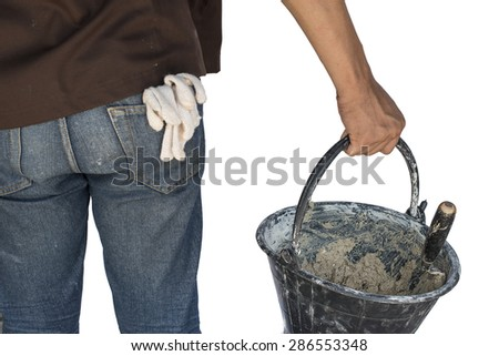 Construction worker holding dirty trowel and bucket with mortar on construction. isolated - stock photo