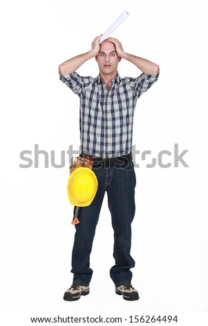 Construction worker holding his head in horror - stock photo