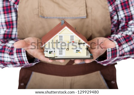 Construction worker holding house model. Isolated on white background - stock photo