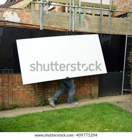 Construction worker holding plasterboard - stock photo
