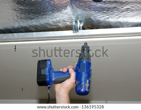 Construction worker holding the hand drill - stock photo