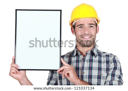 Construction worker holding up a blank bulletin board - stock photo