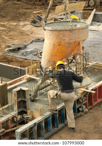 Construction worker in action: concrete being poured into the foundation - stock photo