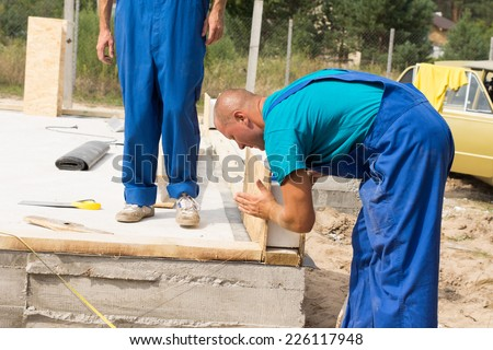 Construction worker in colorful blue overalls lining up insulated wooden wall panels on the foundation of a new build house watched by a co-worker - stock photo