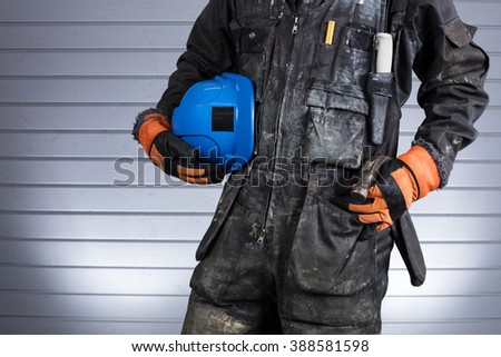 Construction worker in dirty overalls in Finland. The laborer have orange gloves, blue helmet and hammer. Background out of focus and illuminated with flash.  - stock photo