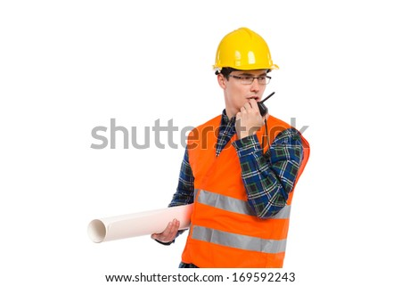 Construction worker in glasses holds paper roll and using walkie-talkie. Full length studio shot isolated on white.